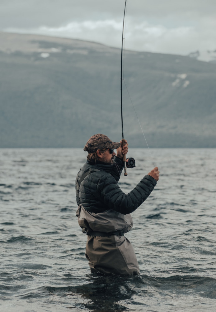 Man in water with fishing rod Trout fishing